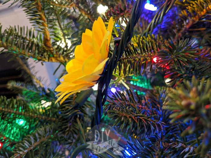 The fake sunflower stem can be inserted into the cords of your Christmas lights.