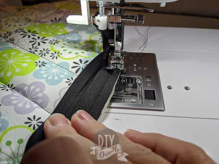 Double fold bias tape being sewn onto a pot holder that has purple, green and blue floral print.