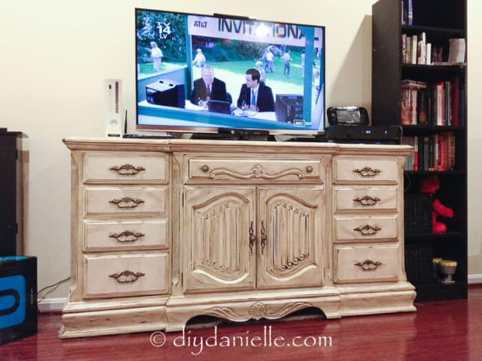 Rustic white distressed tv stand made from a bureau. TV on top.