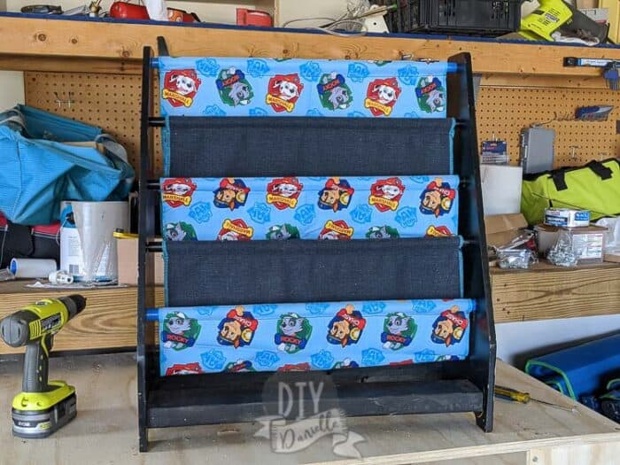 Repaired sling bookshelf sitting on top of a toolbench with tools nearby. Paw Patrol and matching dark blue fabric for the slings.