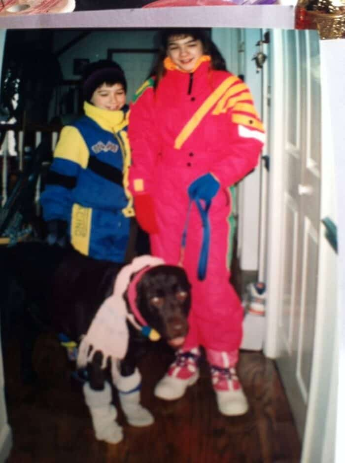Picture of Danielle in the 1980s in full 80's snow gear and big hair. Dog and brother dressed up too!