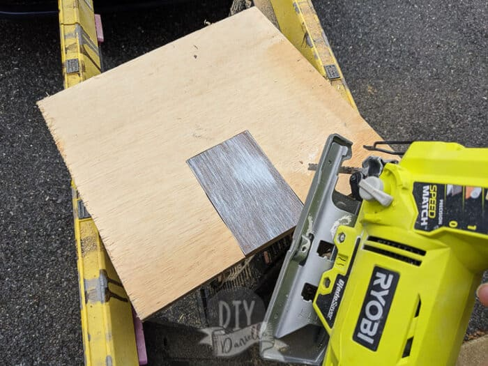 Using a jig saw to cut the back door out for the toy barn.