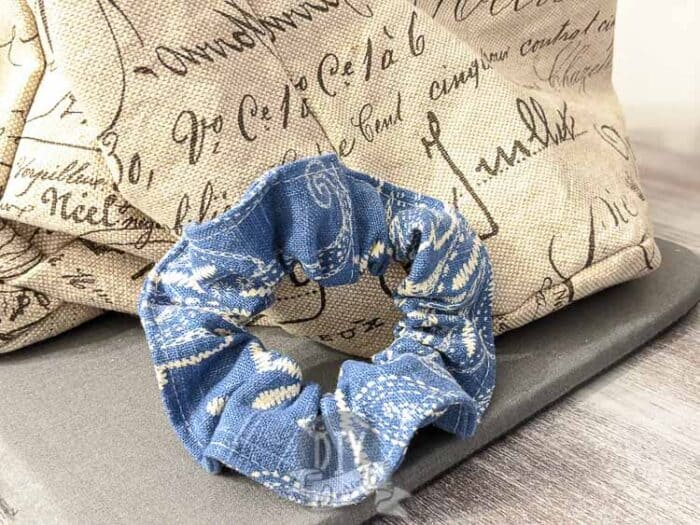 Blue and white scrunchie that was handmade, laying against some burlap.