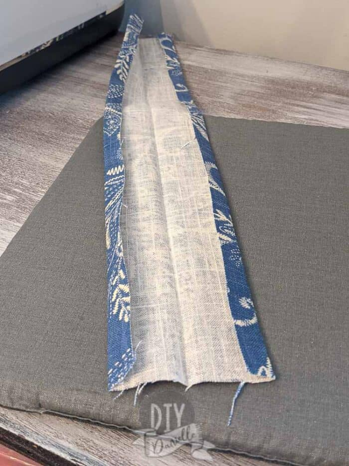 """Folding over the long edges of the 20"""" strip of fabric by approx 1/4""""."""