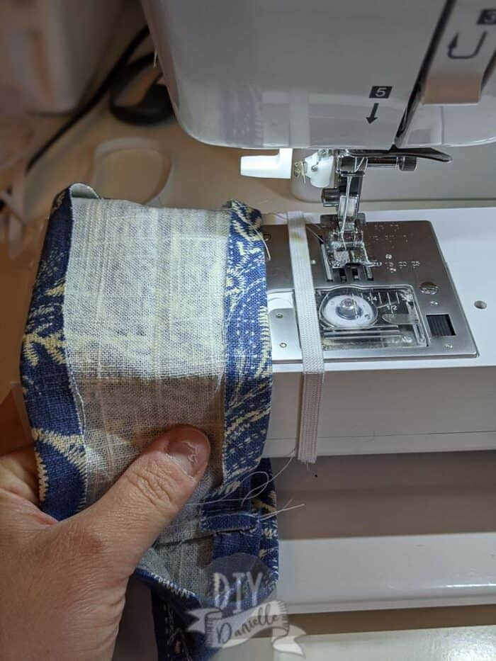 Placing elastic around the arm of the sewing machine. Fabric next to it.