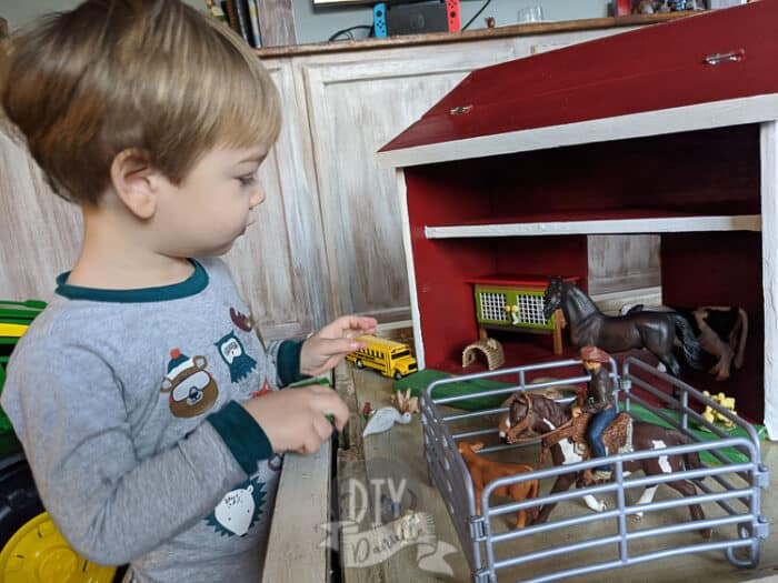 My 2 year old son playing with the wood barn and some Schleich toys.