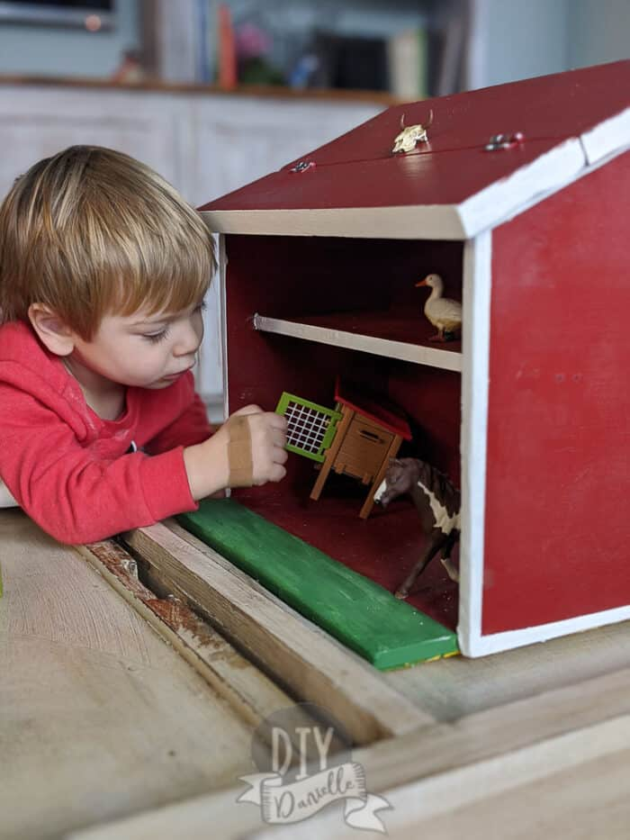 Little boy playing with a wood toy barn painted red with white trim. Farm animals inside the barn include a duck, rabbit hutch, and a horse.