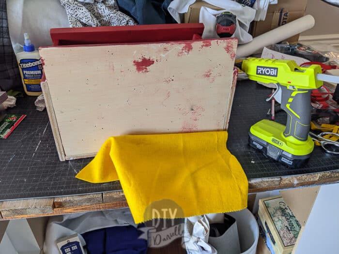 Adding yellow felt to the bottom with my hot glue gun.