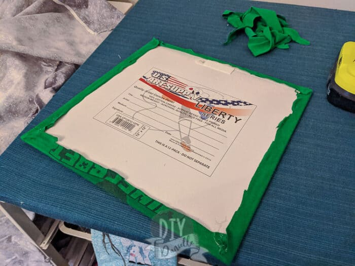 The shirt is glued onto the back of the canvas panel.