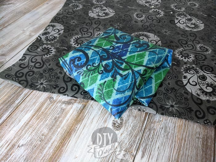 Two beeswax wraps for sandwiches, one folded and one flat underneath.