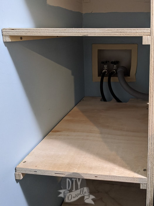 Placing shelves and a support along the wall for the other side of the shelf.