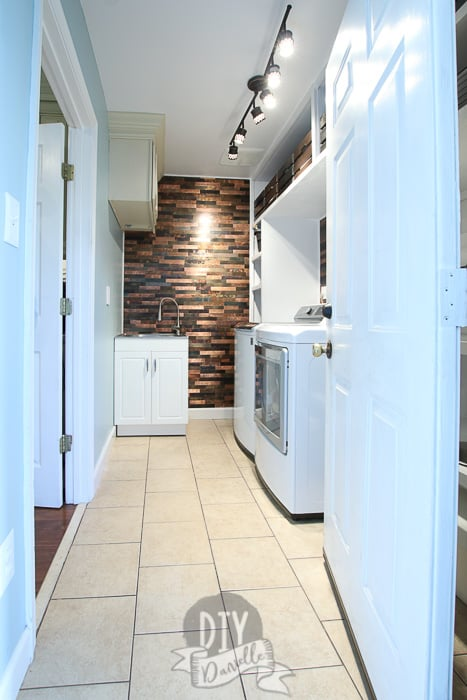 Laundry/mudroom with custom white plywood shelving, a small white sink, and metallic backsplash wall. The door to room is open.