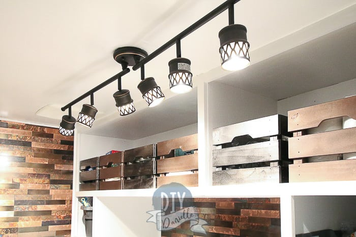 Rubbed bronze track lighting for laundry room adds a lot of light. Storage bins painted metallic colors on the top mudroom shelves.