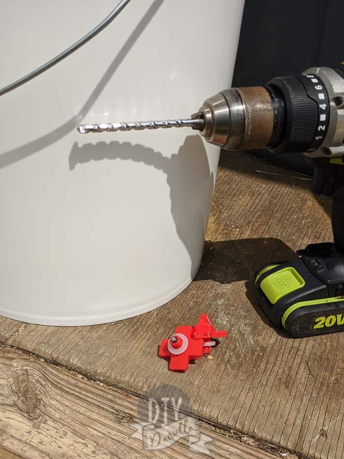 Supplies for a diy chicken water bucket. Drill with bit, chicken nipples.