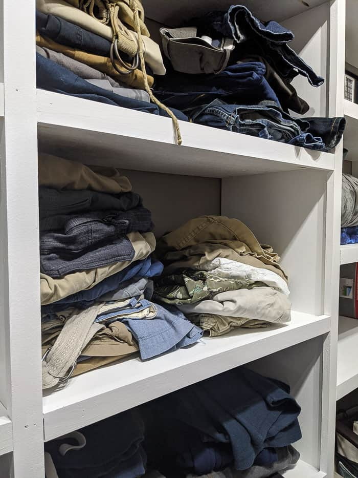 1x2s used as trim on closet shelves. Shelves full of folded mens pants and short.