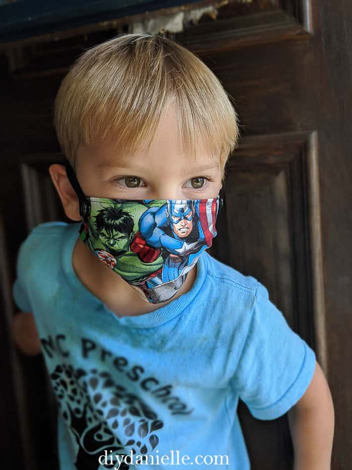 3 year old boy with blond hair wearing a super hero DIY kids mask with snaps on either side so they can breakaway in an emergency.