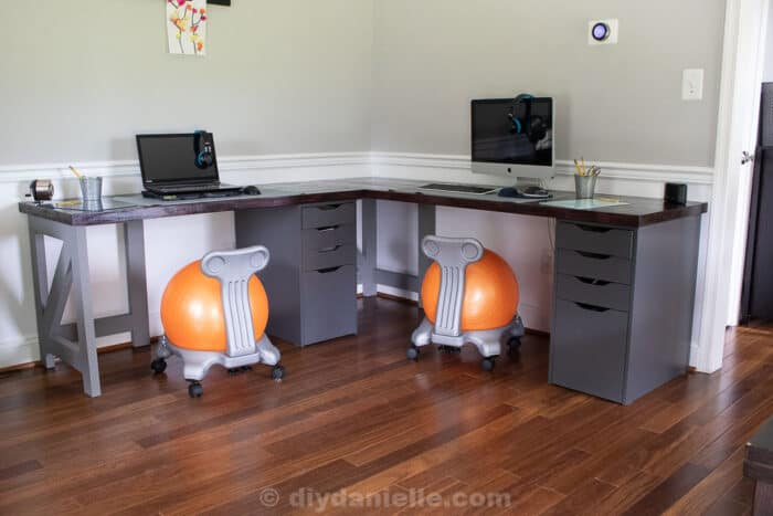 DIY 2 person corner desk for a kid's homeschooling area. Two computers, two yoga ball chairs, butcherblock countertops and gray Alex drawers from IKEA.