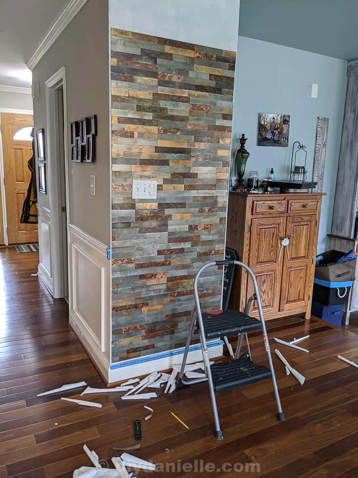 Picture of the peel and stick metal tiles on the feature wall, about 80% done with no trim on yet. Note the gap around the outside of the tile to place the trim.