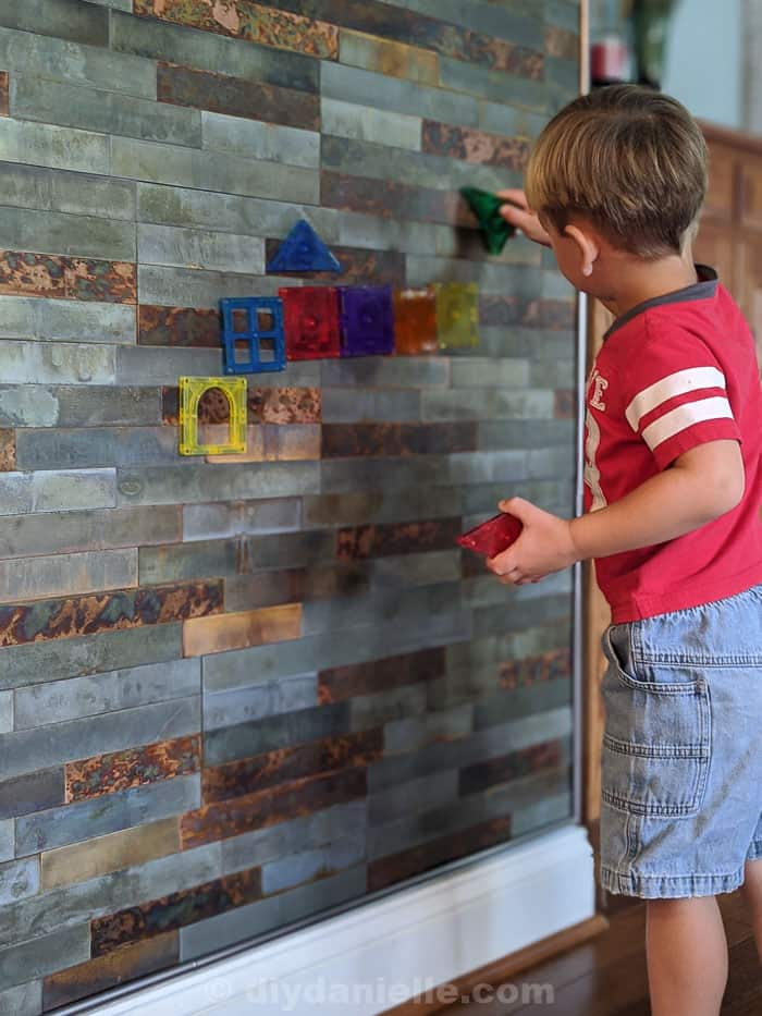 Distressed metal stick on tiles with toddler boy placing magnetiles on the wall.