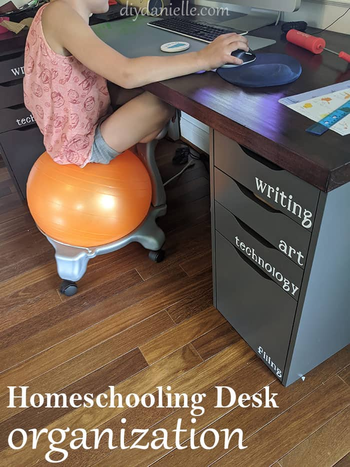 Young boy sitting on a bounce chair while he works on a computer for digital learning. The desk drawers are organized with the labels: Writing, Art, Technology, and Filing.
