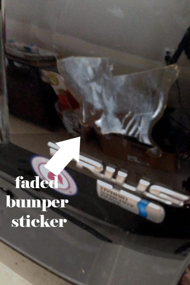 Faded bumper stick peeling off the back of a Black Prius