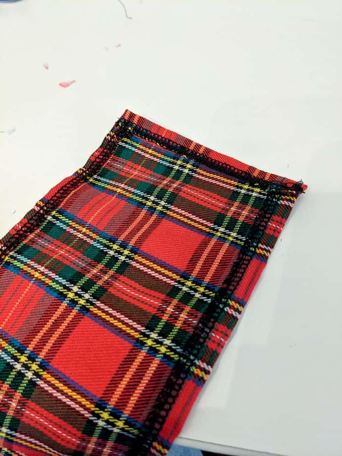 Piece of plaid fabric hemmed on three sides.