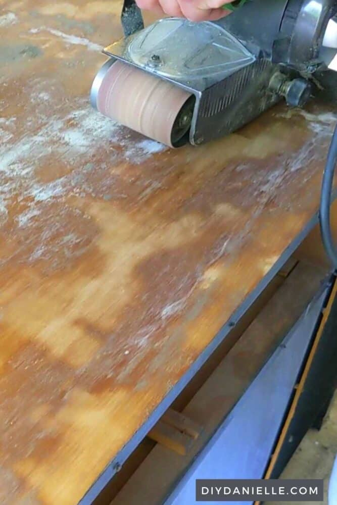 Using a belt sander to finish sanding the top of the desk.