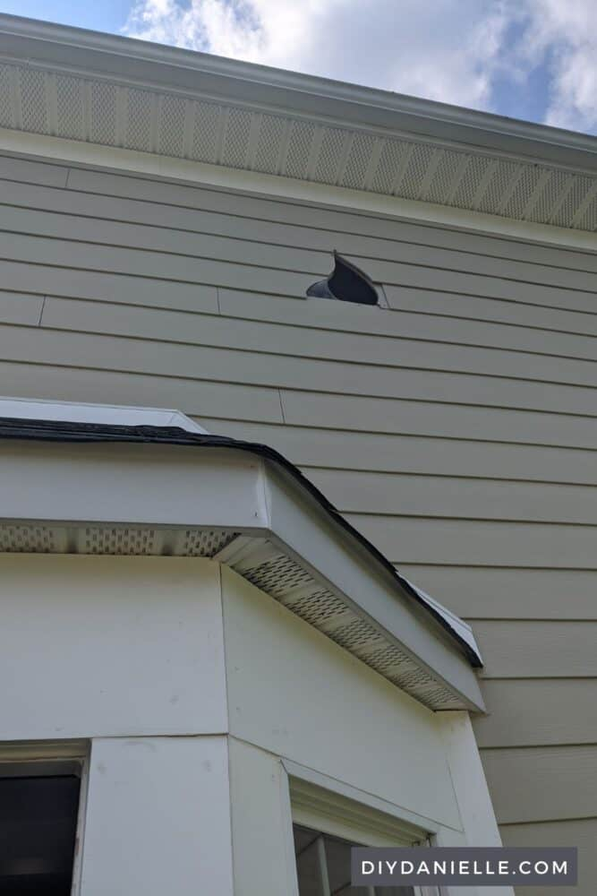 Photo of a hole in the siding, created by the contractor installing the window.
