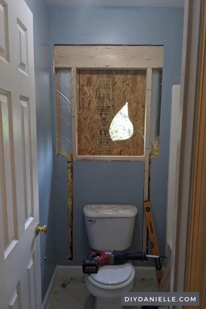 Framing that will go around the window above a toilet. There's a hole where they started cutting away the siding of the house.