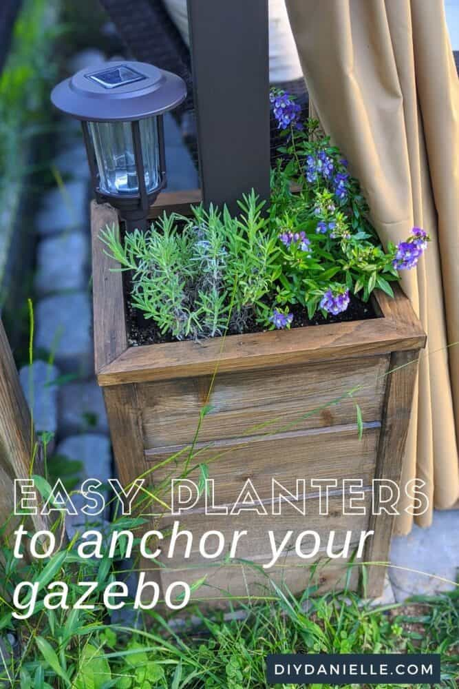 Easy DIY Planters to help anchor your gazebo in the wind. Purple flowers and lavender growing inside the planter with a solar light in the corner.