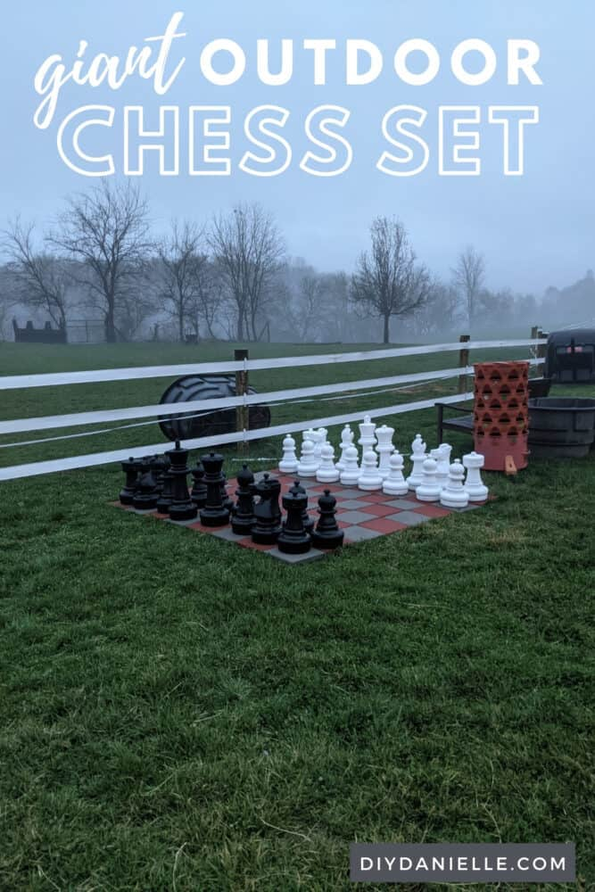 Large outdoor chess board in front of a field.
