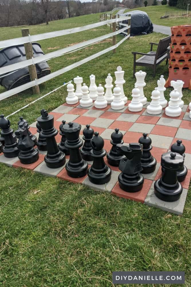 Giant chess board next to a field, a bench, and a garden tower.