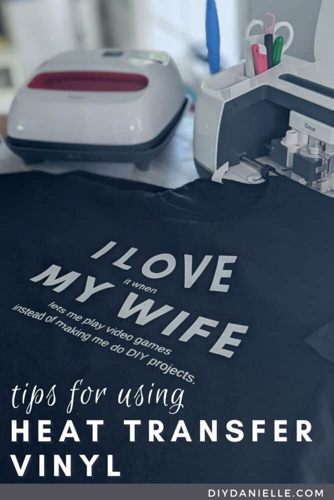 """How to apply iron on vinyl: a guide to HTV. Photo of a Cricut Maker and EasyPress with a folded shirt that says """"I love it when my wife lets me play video games instead of making me do DIY projects."""""""