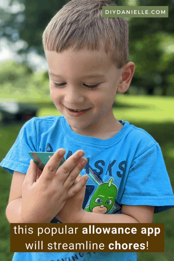 This popular allowance app for kids will streamline chores. Photo of a blond toddler in a blue shirt holding a debit card in his hands and looking at it with a smile on his face.