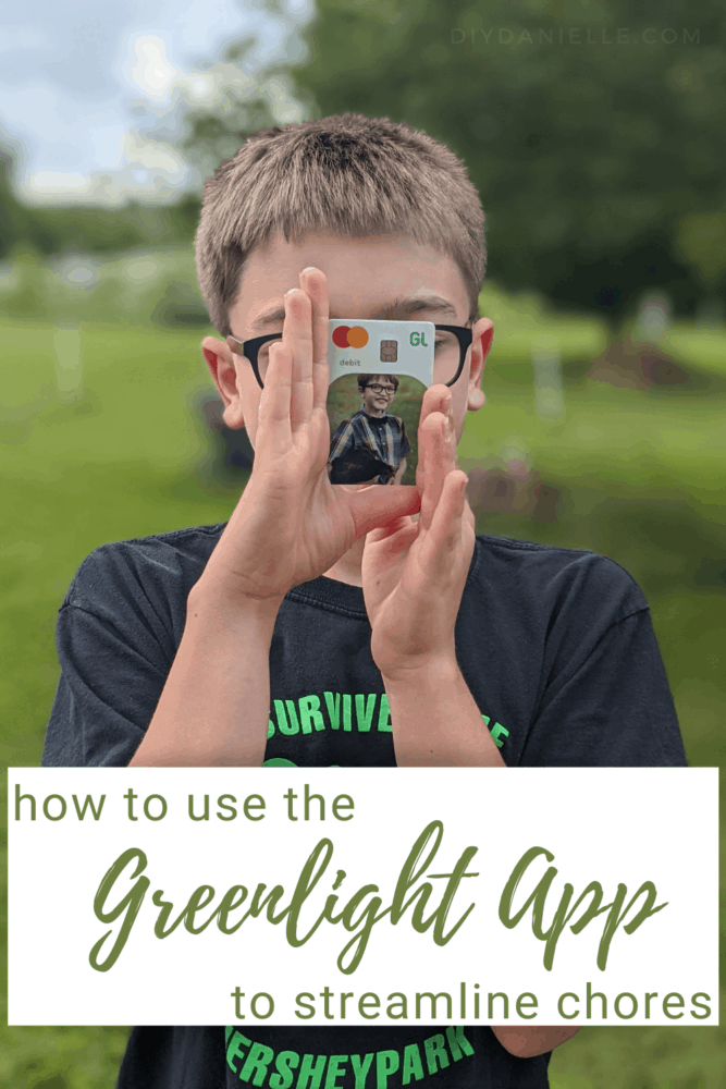 How to use the Greenlight app to help streamline chores. Photo of a 9 year old boy with blond/light brown hair holding a photo debit card from Greenlight. The card has a picture of him holding his pet chicken.
