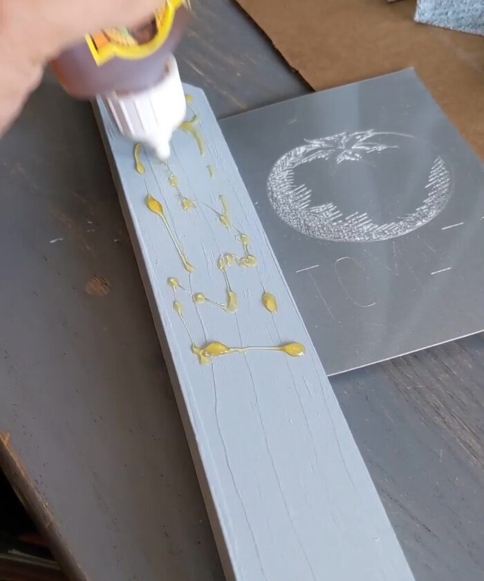 Using Gorilla Glue to adhere the engraved metal pieces to the wood stakes.