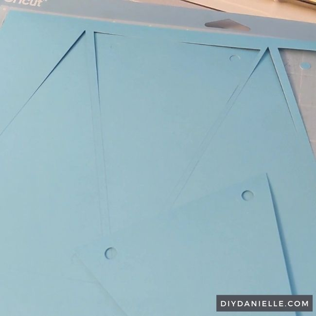Triangles on light blue cardstock with the holes cut out for threading the yarn for the banner through.