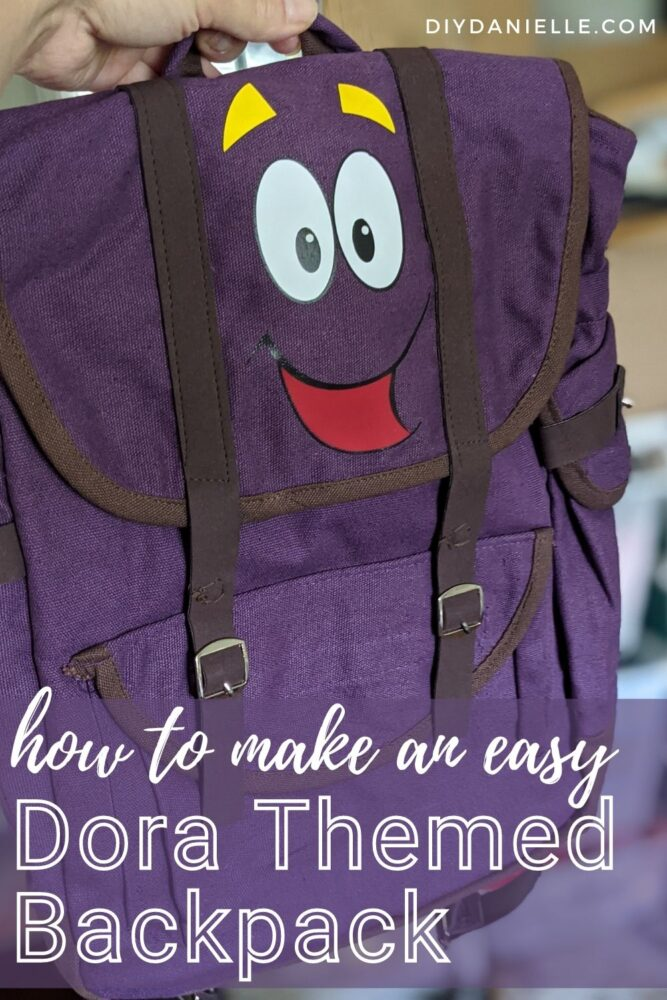 How to make an Easy Dora Themed Backpack. Purple backpack with a cartoon face heat pressed onto the front flap.