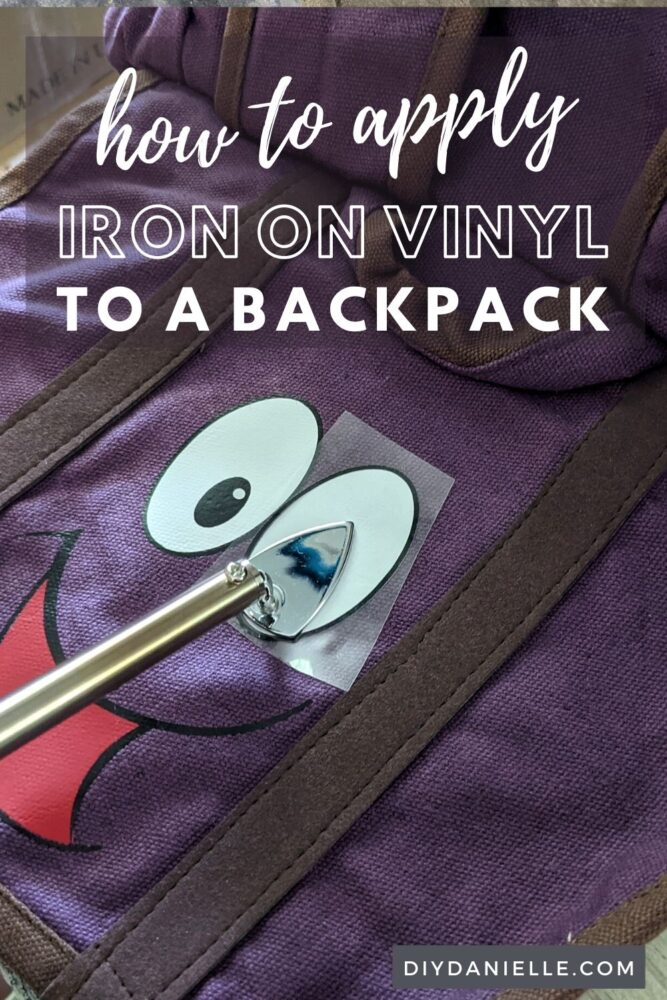 How to apply iron on to a backpack to customize it. Close up photo of a purple backpack with a face of HTV/iron on vinyl being added with the Clover minipress.
