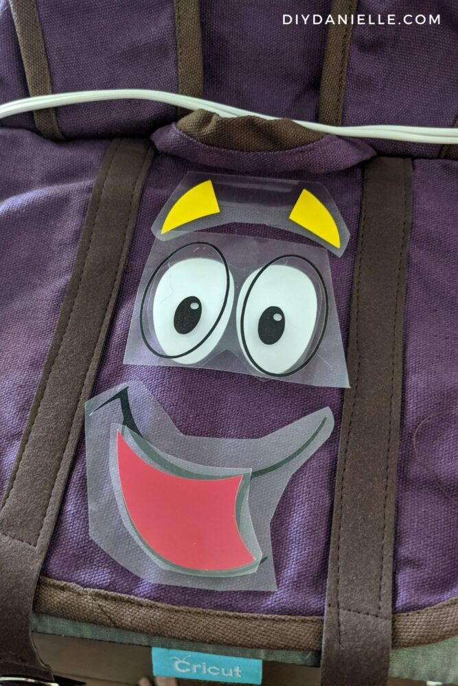 Iron on vinyl design weeded and placed on the front of a backpack to make sure they fit between the sewn on straps.