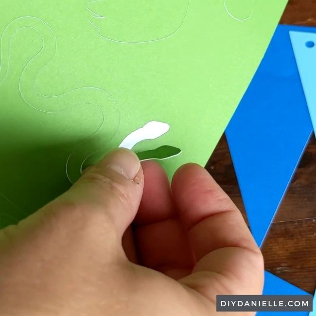 Snake being peeled off lime green sticker cardstock.
